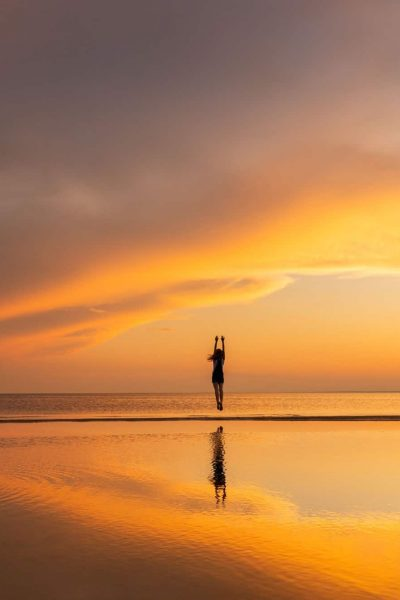 Silhouette of carefree fitness woman jumping on the beach at sunset, raising her hands up. Freedom.